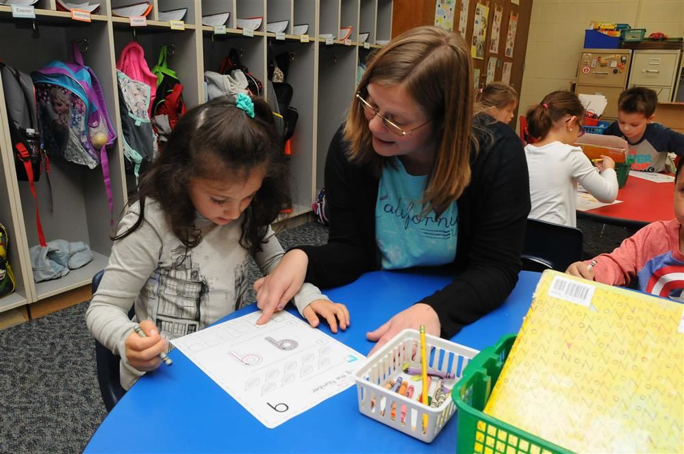 kindergarten teacher and student studying