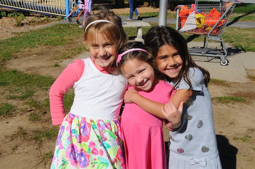 3 girls on playground with arms around each other