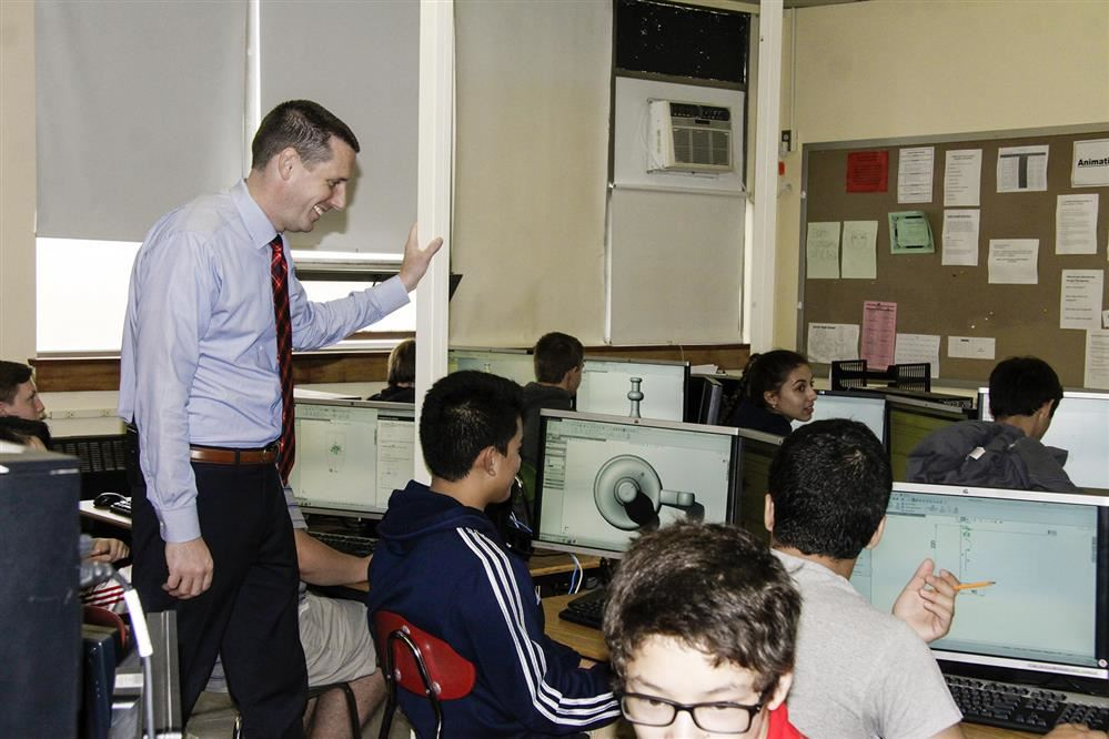 teacher helping students on computers